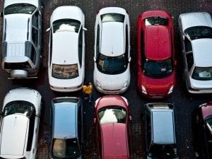 A pedestrian walks past cars at a parkin