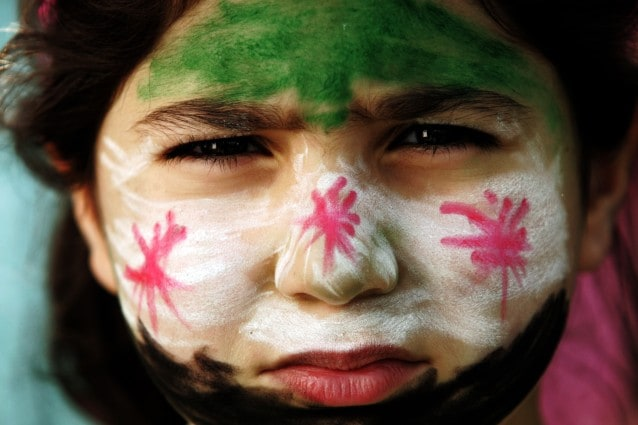 A child with her face painted in the col