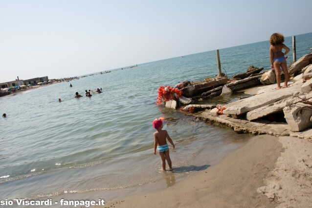 Bagnanti tra le case abusive sommerse dal mare a Bagnara