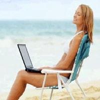 donna in spiaggia con il pc connessione wi-fi gratuita