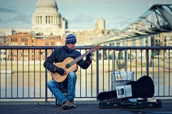 Un musicista di strada, alle spalle il Tate Museum
