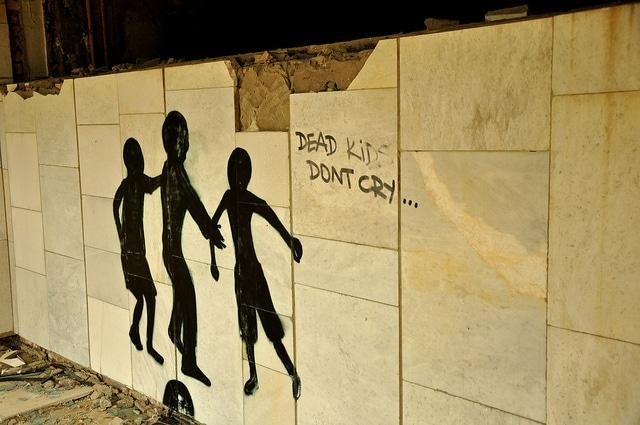 """Sul muro di una scuola, """"non piangete, ragazzi morti"""" (Foto di Jennifer Boyer)."""