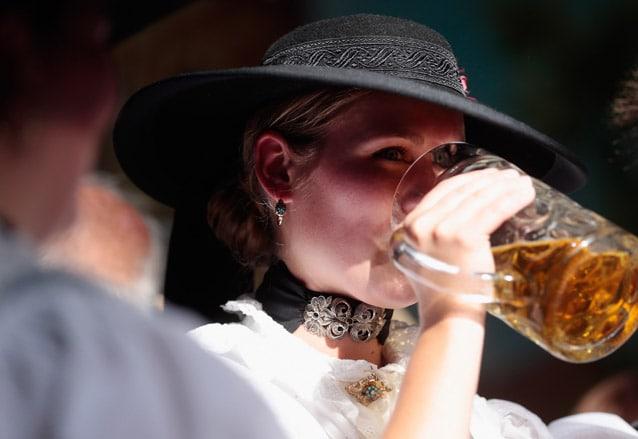 Ragazza vestita nel tipico abito bavarese sorseggia una pinta