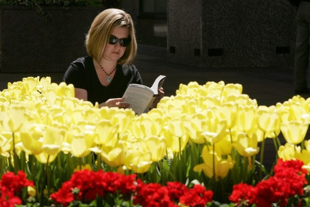 New York, UNITED STATES: A woman reads a book among the Tulips that are planted in the Rockefeller Center promenade 03 May, 2007 in New York. AFP PHOTO/DON EMMERT (Photo credit should read DON EMMERT/AFP/Getty Images)