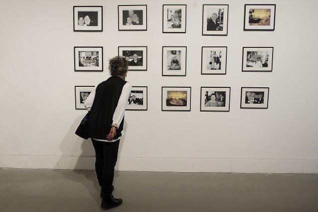 Una visitatrice guarda incuriosita un'opera della Biennale di Venezia.
