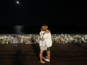 Una coppia si abbraccia sulla Promenade des Anglais davanti a centinaia di mazzi di fiori in ricordo delle vittime dell'attentato (Foto: Getty Images)