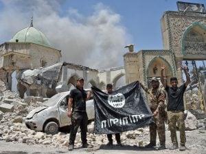 Membri esercito iracheno in posa con bandiera Isis dopo aver liberato Mosul