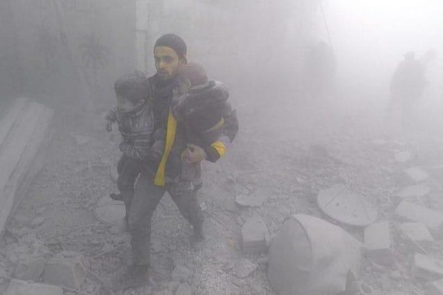 Un uomo cerca di mettere in salvo due bambini dopo un bombardamento a est di Damasco (White Helmets)