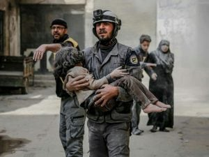 Un volontario dei Caschi bianchi porta in salvo una bambina ferita nei raid sulla Ghouta orientale
