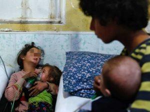 Una bambina tiene la maschera di ossigeno ad una neonata dopo un attacco con gas cloro in Siria (Gettyimages)