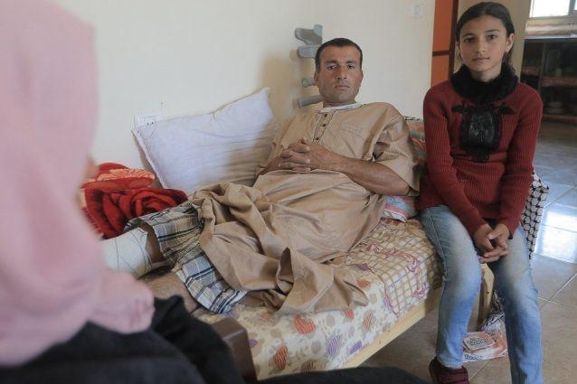 Reham accanto al padre colpito da un cecchino israeliano durante le proteste a Gaza (Ahmed Mashharawi/NRC)