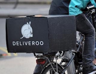 """La denuncia di riders e sindacati: """"Paghe più basse con il nuovo contratto"""". Deliveroo nega"""