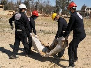 I membri del Comitato per la ricostruzione di Raqqa trasportano i resti ritrovati nello stadio della città. (Human Right Watch)