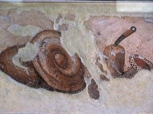"""Mosaico del II secolo a. C. in cui sono raffigurati gli ingredienti principali del """"pane dorato"""" romano: pane e burro."""