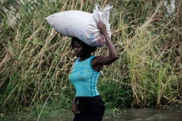 Una donna trasporta un sacco di riso a Beira, una delle città del Mozambico più colpite dal ciclone Idai (Gettyimages)