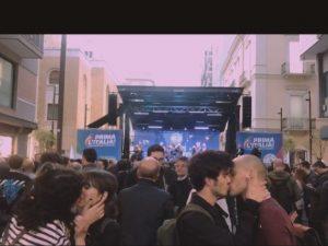 Il bacio fra una coppia di ragazze e una di ragazzi stagliato contro il palco del comizio di Matteo Salvini.
