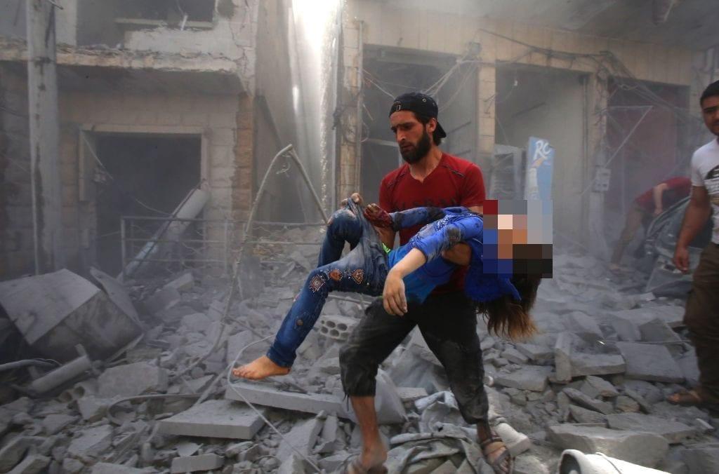 Un uomo cerca di portare in salvo una bimba dopo il bombardamento a Maarrat al–Numan (Gettyimages)
