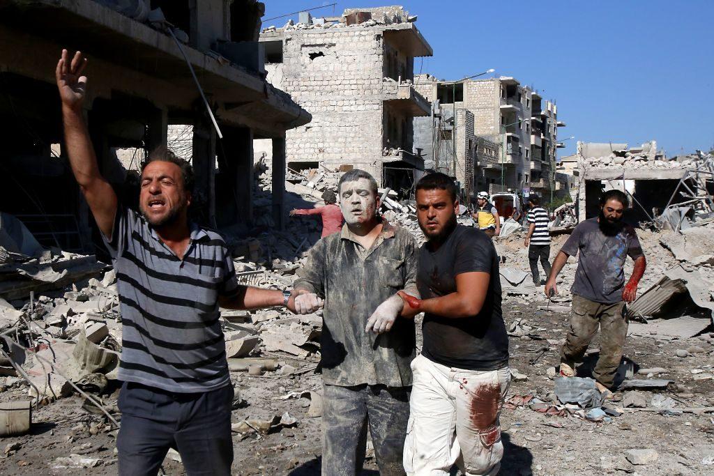 Un uomo viene portato in salvo dopo il bombardamento al mercato di Maarat al–Numan del 22 luglio (Gettyimages)