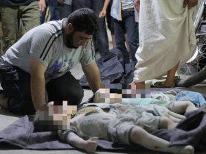La disperazione di un padre davanti ai suoi tre figli uccisi nel bombardamento a Maaret al–Numan (Gettyimages)