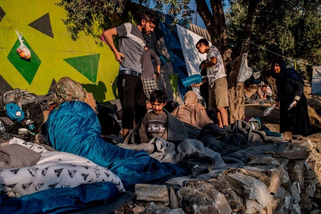 Un gruppo di profughi costretti a dormire fuori dal centro di prima accoglienza di Moria sull'isola greca di Lesbo (Gettyimages)