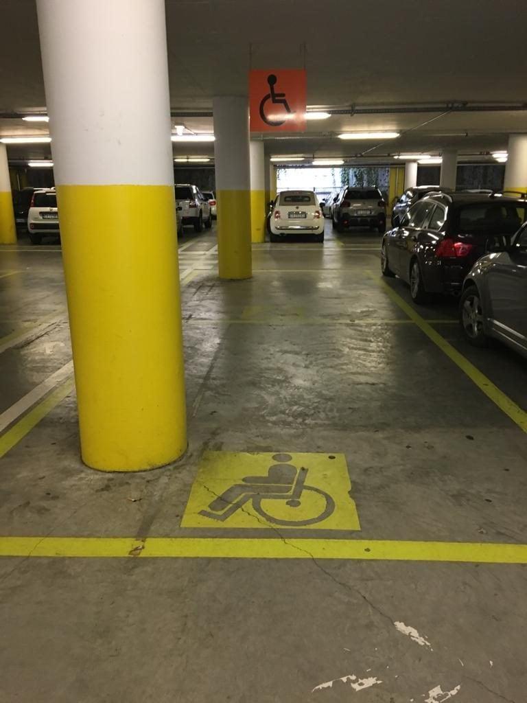 Parcheggio per disabili non a norma, con palo in mezzo e assenza di strisce zebrate gialle per salita–discesa.