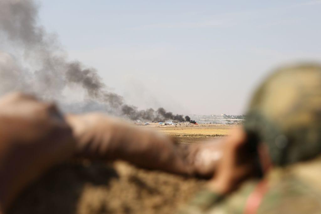 Miliziani dell'Esercito libero siriano schierati accanto alle truppe turche osservano le esplosioni a Ras al–Ain