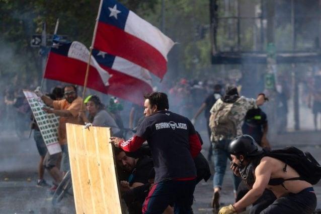Manifestanti nella capitale cilena con la bandiera nazionale (Gettyimages)