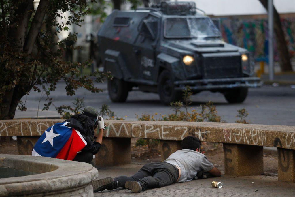 Alcuni manifestanti si nascondono dai militari che pattugliano le strade di Santiago, la capitale cilena (Gettyimages)