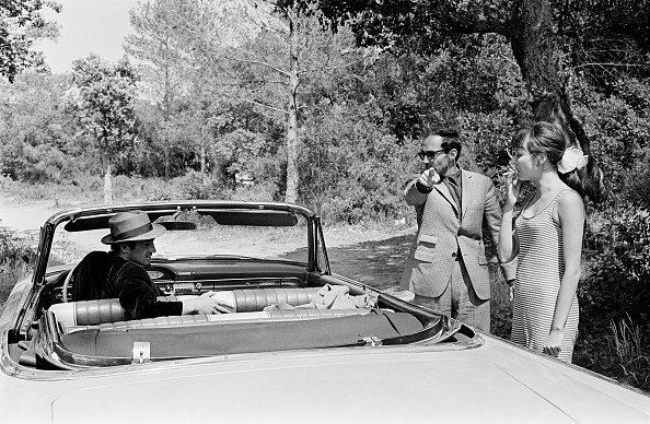 "Il regista Jean-Luc Godard sul set del film ""Pierrot Le Fou"", insieme a Jean-Paul Belmondo e Anna Karina."
