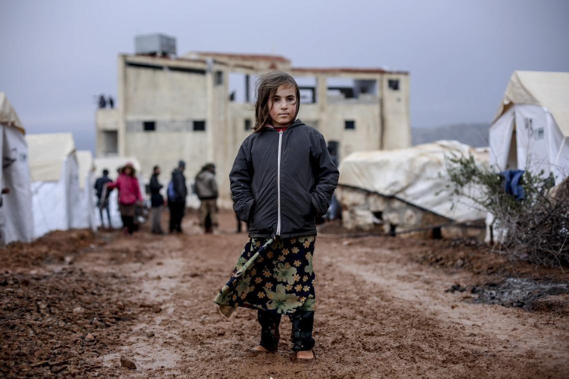 Una bimba siriana in mezzo al fango in un campo per sfollati a nord di Idlib (Khaled Akacha/Unicef)