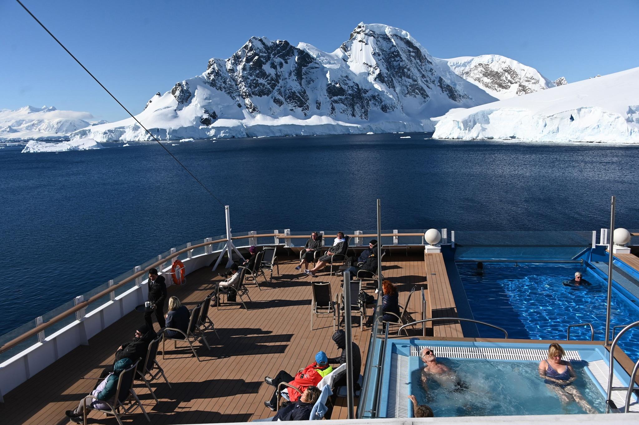 Turisti prendono il sole in piscina di fronte a un ghiacciaio islandese