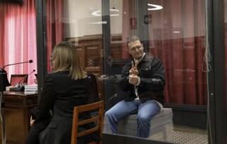 Igor il Russo a processo in Spagna, sorridente fa il segno di vittoria dalla gabbia di vetro