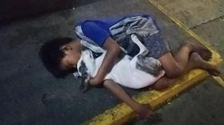 Bimbo senzatetto dorme sul marciapiede abbracciato al cane: la foto simbolo di miseria e amicizia