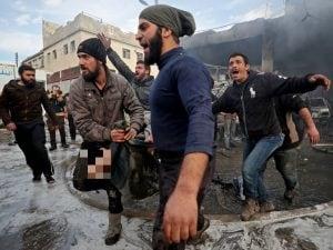 Il corpo senza vita di un uomo, ucciso nel bombardamento al mercato di al–Hal di Idlib, Siria (Gettyimages)