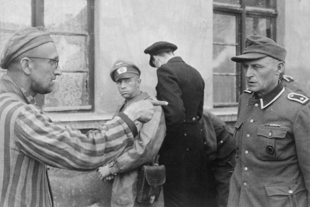 Un schiavo lavoratore russo tra i prigionieri liberati dalla 3a Divisione Corazzata indica una ex guardia nazista che picchiava brutalmente i prigionieri. 14 maggio 1945, Germania Autore sconosciuto o non fornito © courtesy U.S. National Archives and Records Administration