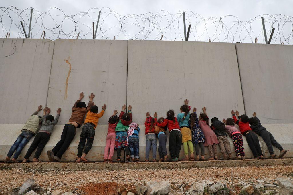 Bambini siriani vicino al muro che delimita la frontiera con la Turchia nella provincia di Idlib (Gettyimages)