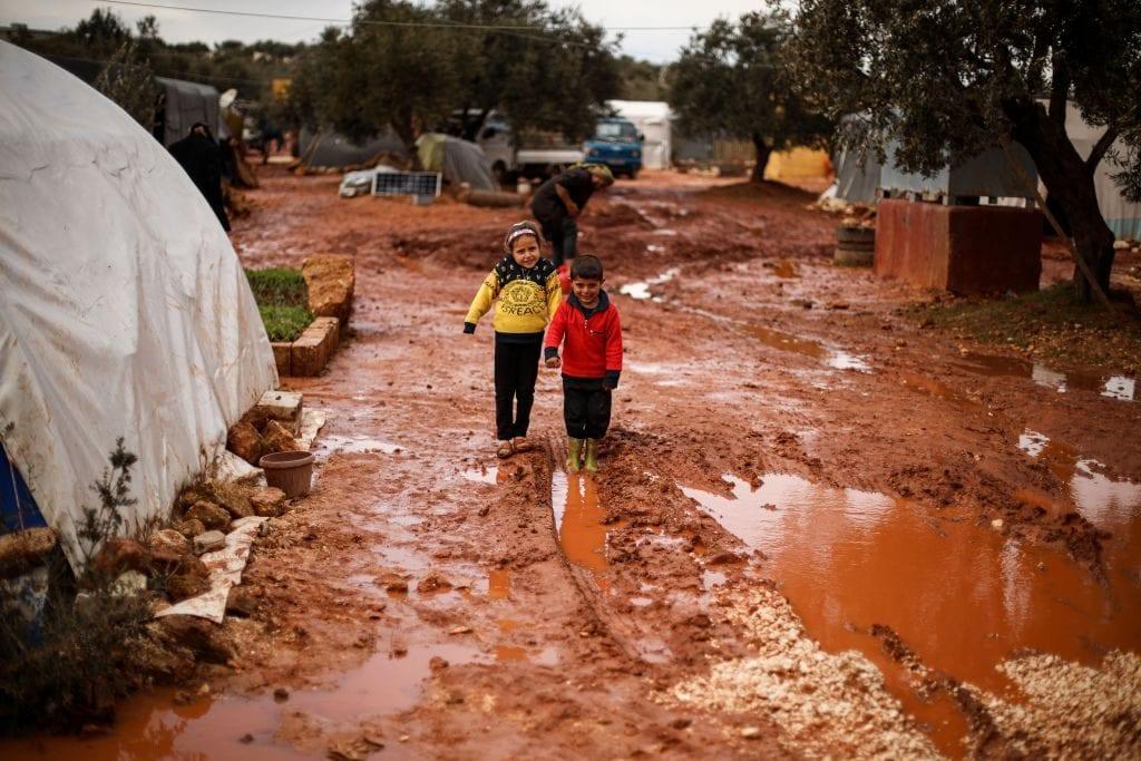 Bimbi tra il fango in un improvvisato campo profughi a nord di Idlib (Gettyimages)