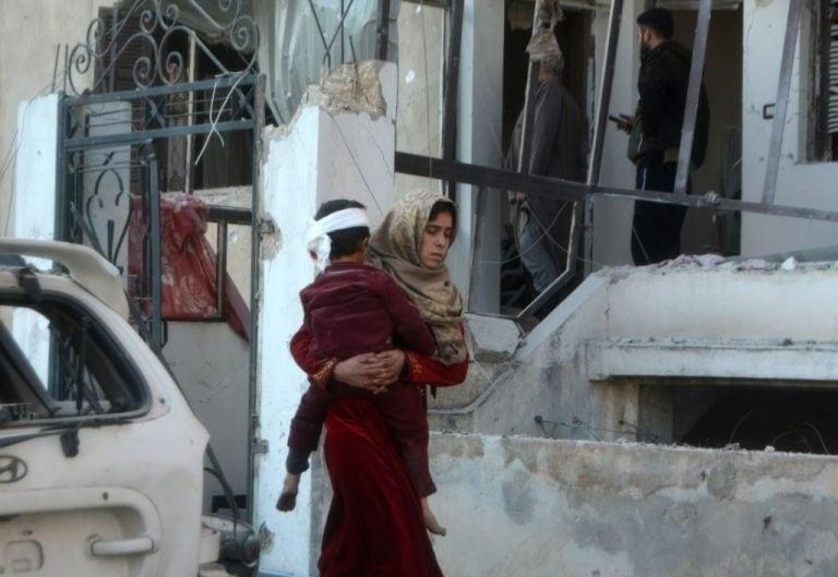 Una donna cerca di mettere in salvo il figlio dopo il bombardamento aMaarrat Misrin (Gettyimages)