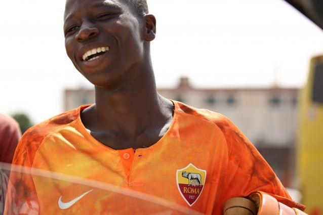 Ragazzo ivoriano venditore ambulante con maglia della A.S. Roma