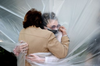 Il primo abbraccio di Olivia alla nonna dopo 3 mesi di lockdown attraverso un telo di plastica