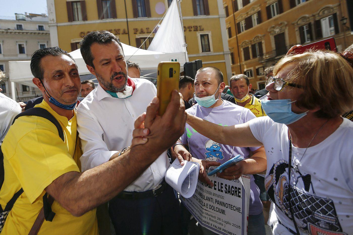 Salvini in mezzo ai manifestanti: pur non rispettando la distanza di un metro, abbassa la mascherina.