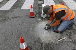 Riempie le buche della città con un mosaico: quando si dice arte di strada