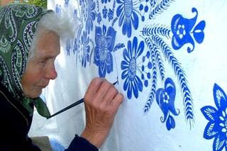 A 90 anni decora da sola tutte le case del villaggio: la ragione è commovente