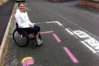 La scuola della figlia non le fornisce il parcheggio per disabili, lei lo disegna da sola