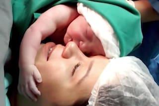 Appena nata abbraccia il viso della sua mamma, l'attimo è emozionante