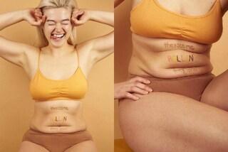 """Fiera dei """"rotolini"""": la modella mostra con orgoglio la sua pancia non piatta"""