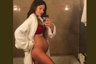 Nuda e senza slip davanti allo specchio, le futura mamma mostra il pancione