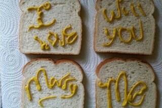"""Scrive """"Vuoi sposarmi?"""" sul pane tostato con la mostarda: la proposta di nozze più originale"""