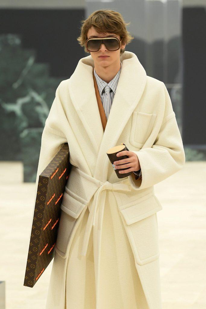 Un modello sulla passerella di Louis Vuitton con un cappotto a vestaglia bianco panna