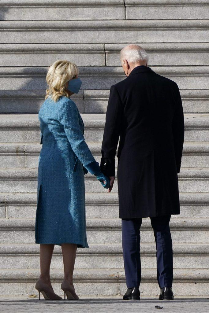Jill Biden con l'abito azzurro dà la mano al marito Joe Biden